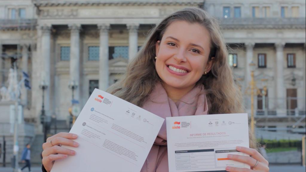 Daniela auluna do Instituto Aprender Espanhol Online segurando o certificado de espanhol do siele